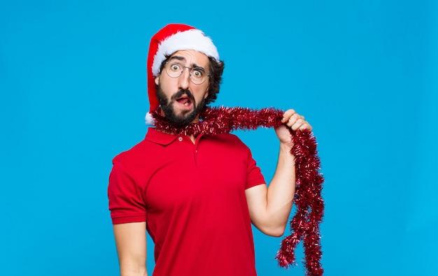 Молодой сумасшедший бородатый человек с шляпу санта. рождественская концепция