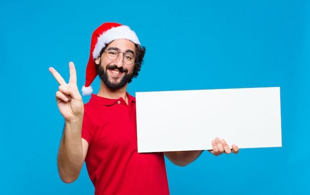 サンタの帽子を持つ若い狂気のひげを生やした男。クリスマスのコンセプト