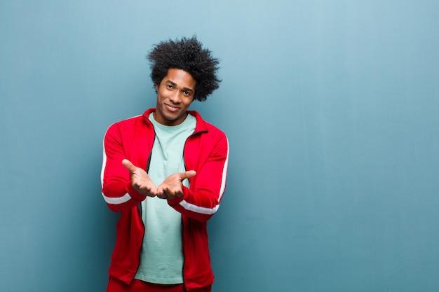 Молодой черный спортивный человек счастливо улыбается с дружелюбным, уверенным, позитивным взглядом, предлагая и показывая объект или концепцию против гранж