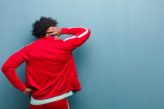 Молодой черный спортивный человек думает или сомневается, почесывая голову, чувствуя себя озадаченным и смущенным, вид сзади или сзади против гранж