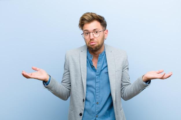 Молодой бизнесмен чувствует себя невежественным и растерянным, не уверенным, какой выбор или вариант выбрать, удивляясь голубому