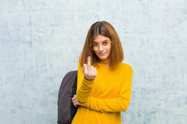 怒り、イライラ、反抗的、攻撃的な感じ、中指を弾く、グランジに対して反撃する若い学生女性