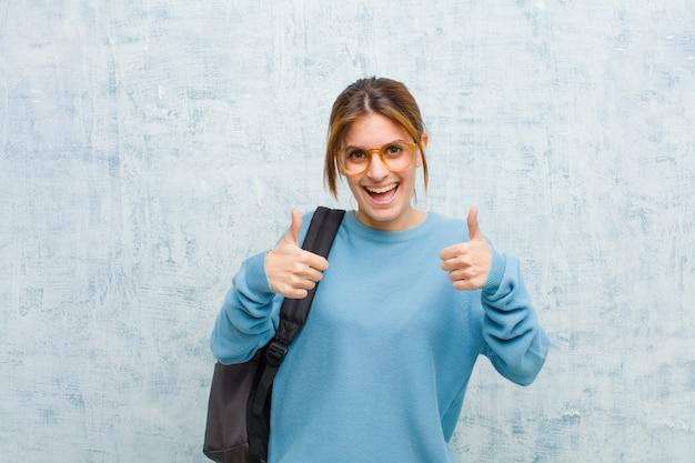 Молодой студент женщина улыбается широко глядя счастливым, позитивным, уверенным и успешным, с двумя большими пальцами против гранж