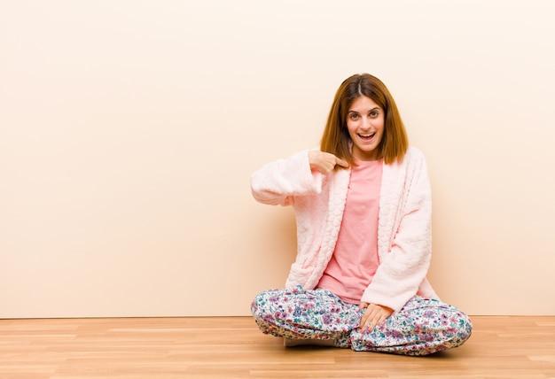 自宅で座っているパジャマを着た若い女性は幸せ、誇りと驚きを探して、元気に自己を指して、自信と高尚さを感じます