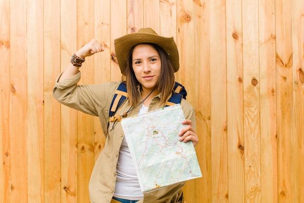 Молодая женщина путешественника с картой против древесины