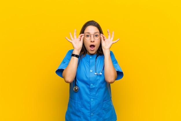黄色に対して隔離された驚いた、信じられない表情でメガネを保持している、ショックを受け、驚き、驚きを感じる