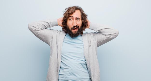 ストレス、心配、心配、怖い、頭の上の手で、フラットカラーに対して誤ってパニックを感じる若いひげを生やした狂気の男