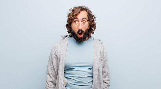 若いひげを生やした狂気の男は非常にショックまたは驚きを探して、フラットカラーに対してすごいと言って口を開けて見つめて