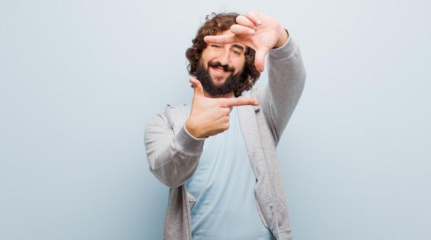 Молодой бородатый сумасшедший, чувствуя себя счастливым, дружелюбным и позитивным, улыбаясь и делая портретную или фоторамку руками против плоского цвета