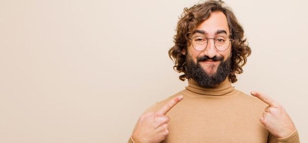 Молодой бородатый сумасшедший, уверенно улыбающийся, указывая на собственную широкую улыбку, позитивное, расслабленное, довольное отношение к ровному цвету