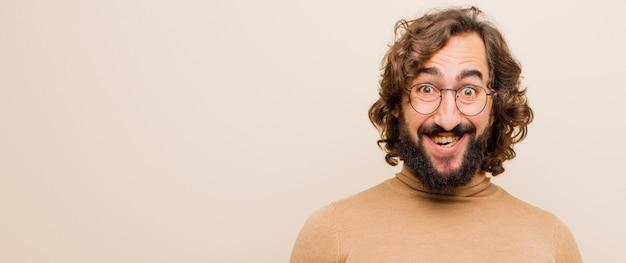 Молодой бородатый сумасшедший мужчина выглядит счастливым и глупым с широкой, веселой, чокнутой улыбкой и широко открытыми глазами на плоском цвете