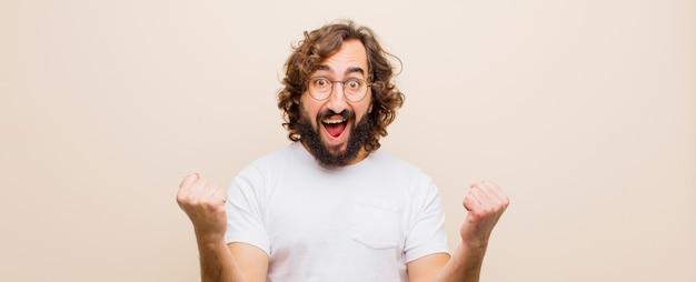 Молодой бородатый сумасшедший чувствует себя счастливым, позитивным и успешным, празднует победу, достижения или удачу на фоне плоского цвета
