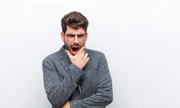 若いマネージャーの男の口と目を大きく開いて、あごに手、不快にショックを感じて、何を言って