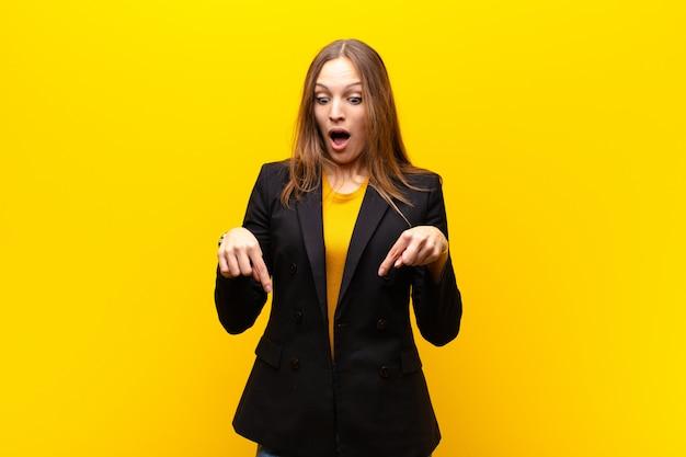 Молодая красивая деловая женщина чувствует себя шокированной, с открытым ртом и изумлением, смотрит и указывает вниз в неверии и удивлении против апельсина