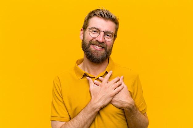 ロマンチックな、幸せ、愛の気持ち、元気に笑顔とオレンジに対して心の近くに手を繋いでいる若い金髪男