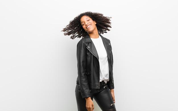 Молодая красивая черная женщина танцует носить кожаную куртку против белых
