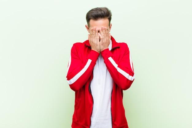 若いハンサムなスポーツ男またはモニターの悲しみ、イライラ、神経質、落ち込んで、両手で顔を覆って、フラットに対して泣いて