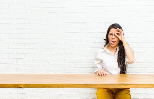 テーブルの前に座っている秘密をスパイ、冗談と覗き穴を通して見る面白い顔で幸せそうに笑って若いかなりラテン女性