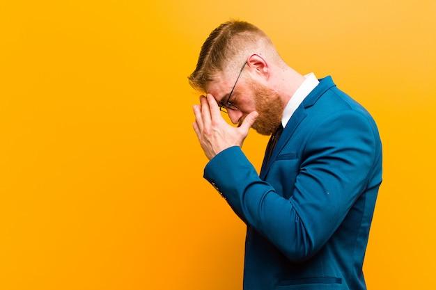 Молодой рыжий бизнесмен, охватывающий глаза руками с грустным, разочарованным взглядом отчаяния, плача, вид сбоку против апельсина
