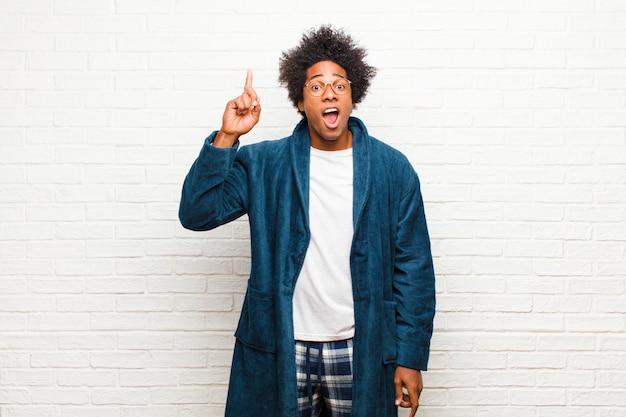 Молодой темнокожий мужчина в пижаме с платьем, чувствуя себя счастливым и взволнованным гением после воплощения идеи, весело поднимая палец, эврика! к кирпичной стене
