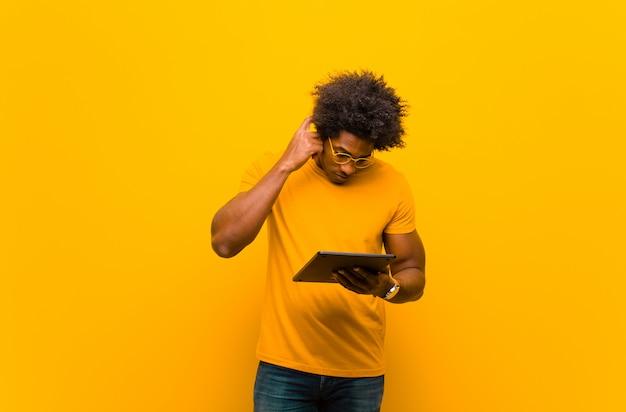 オレンジに対してタブレットで若いアフリカ系アメリカ人