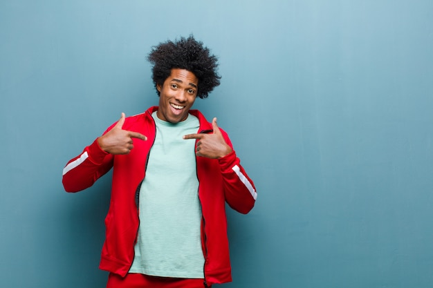 幸せ、驚き、誇りに思って、黒の壁に対して興奮して、驚いた表情で自己を指している若い黒人スポーツ男