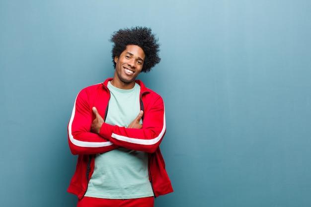 Молодой черный спортивный человек, счастливо смеющийся со скрещенными руками, в расслабленной, позитивной и довольной позе у гранжевой стены