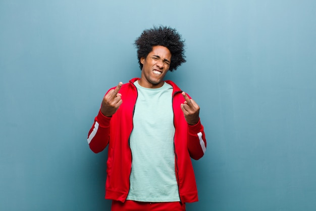 Молодой черный спортивный человек, чувствуя себя провокационным, агрессивным и непристойным, щелкает средним пальцем, с бунтарским отношением к стене гранж