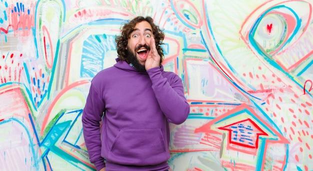 Молодой бородатый сумасшедший, чувствуя себя счастливым, взволнованным и позитивным, кричит руками у рта, кричит против граффити