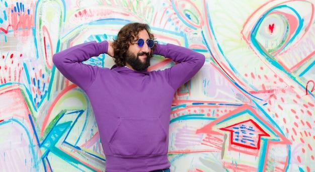 Молодой бородатый сумасшедший, улыбающийся и чувствующий себя расслабленным, удовлетворенным и беззаботным, позитивно смеющийся и пугающий граффити