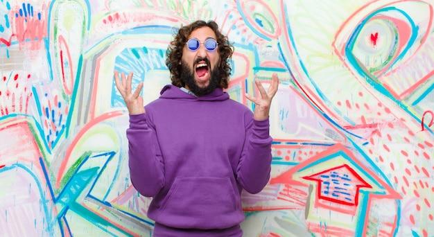 Молодой бородатый сумасшедший человек яростно кричит, чувствуя напряжение и раздражение, поднимая руки вверх, говоря, почему я против граффити