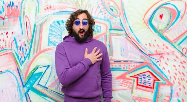 Молодой бородатый сумасшедший чувствуя себя шокированным и удивленным, улыбается, беря руку к сердцу, счастлив быть тем или выражает благодарность против граффити