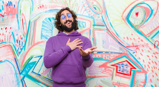 Молодой бородатый сумасшедший, чувствуя себя счастливым и влюбленным, улыбаясь одной рукой рядом с сердцем, а другой растянулся вперед против граффити