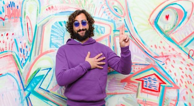 Молодой бородатый сумасшедший смотрит счастливым, уверенным и заслуживающим доверия, улыбается и показывает знак победы, с позитивным настроем против граффити