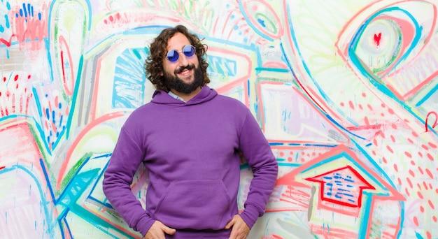 Молодой бородатый сумасшедший, весело и небрежно улыбающийся с позитивным, счастливым, уверенным и расслабленным выражением на фоне граффити