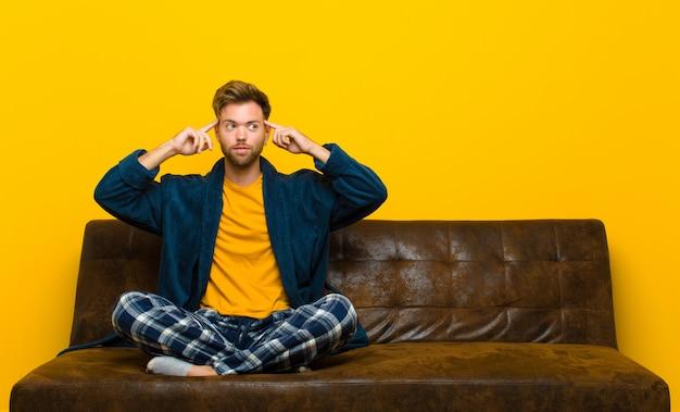 混乱や疑いを感じているパジャマを着ている若い男、アイデアに集中し、一生懸命考えて、側のスペースをコピーしよう