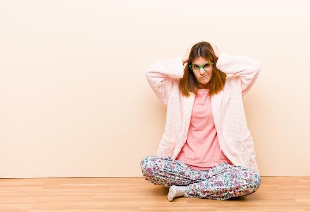 自宅で座っているパジャマを着た若い女性は、イライラし、イライラし、病気になり、失敗に疲れ、退屈で退屈な仕事にうんざりしています