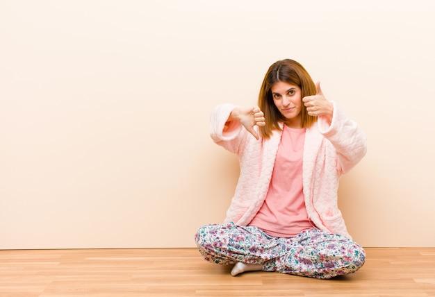 自宅で座っているパジャマを着た若い女性は、混乱し、無知で、自信がなく、さまざまなオプションや選択肢で善と悪の重みを感じています