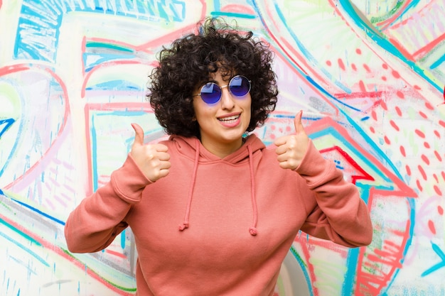 Молодая симпатичная афро женщина улыбается широко глядя счастливым, позитивным, уверенным и успешным, с большими пальцами против граффити