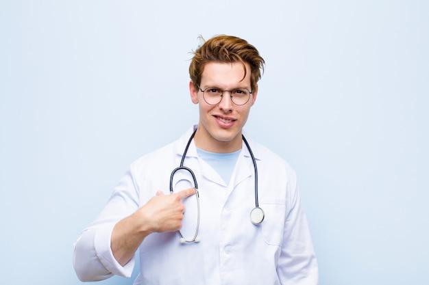 幸せ、誇りに思って、驚いて、元気に自己を指して、青に対して自信と高尚を感じて若い赤ヘッド医師