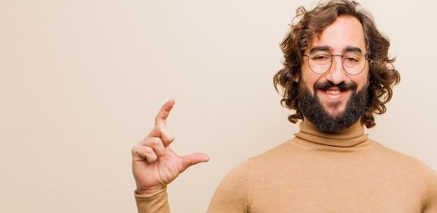 Молодой бородатый сумасшедший мужчина, обрамляющий или обрисовывающий в общих чертах собственную улыбку обеими руками, выглядящий позитивным и счастливым, концепция здоровья на фоне плоской цветной стены