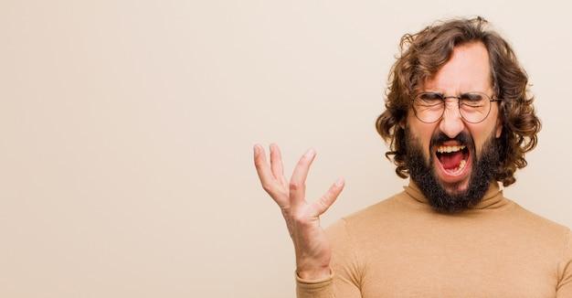Молодой бородатый сумасшедший человек яростно кричит, чувствуя напряжение и раздражение, поднимая руки вверх, говоря, почему я против плоской цветной стены