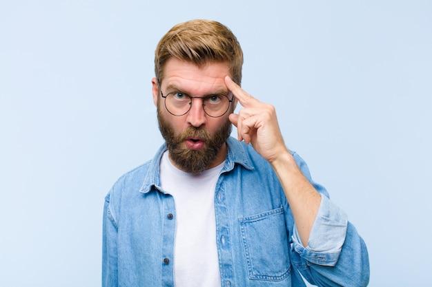 驚いて、口を開けて、ショックを受けて、新しい思考、アイデアや概念を実現している若い金髪の成人男性