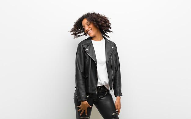 Молодая красивая черная женщина танцует носить кожаную куртку против белой стене