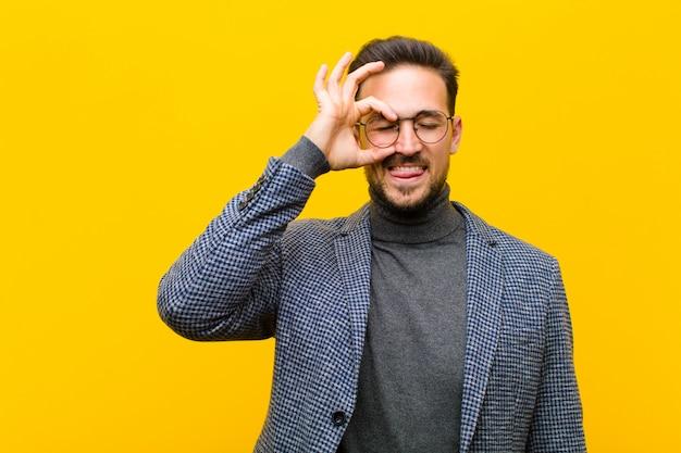 オレンジ色の壁に秘密をスパイ、冗談と覗き穴を通して見る面白い顔で幸せそうに笑っている若いハンサムな男