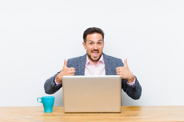 Молодой красивый бизнесмен, улыбаясь широко глядя счастливым, позитивным, уверенным и успешным, с обоими пальцами вверх