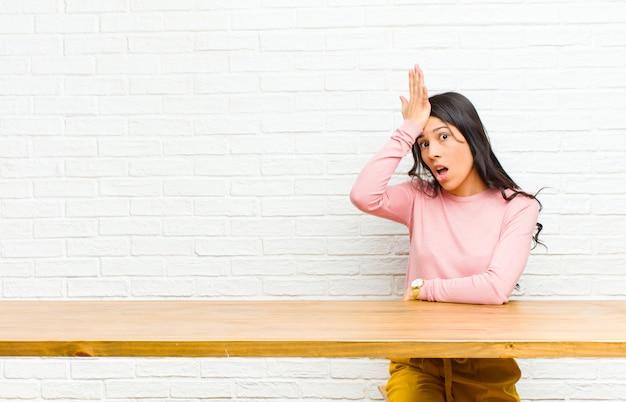 愚かな間違いをしたり、思い出した後、テーブルの前に座って愚かな感じの後、額を考えておっとに手のひらを上げる若いかなりラテン女性