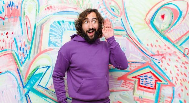 Молодой бородатый сумасшедший улыбается, с любопытством смотрит в сторону, пытается послушать сплетни или подслушивает секрет на граффити стене
