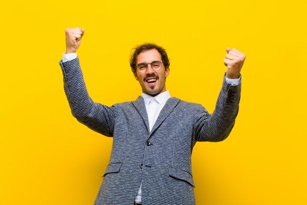 Молодой красавец торжествующе кричит, выглядит как возбужденный, счастливый и удивленный победитель, празднуя на оранжевой стене