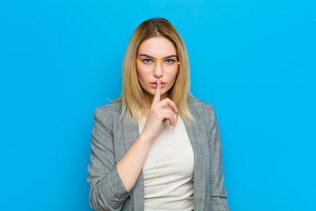 深刻な探している若いブロンドの女性と指で押された唇に沈黙を要求するか、静かに、青い壁に秘密を守る